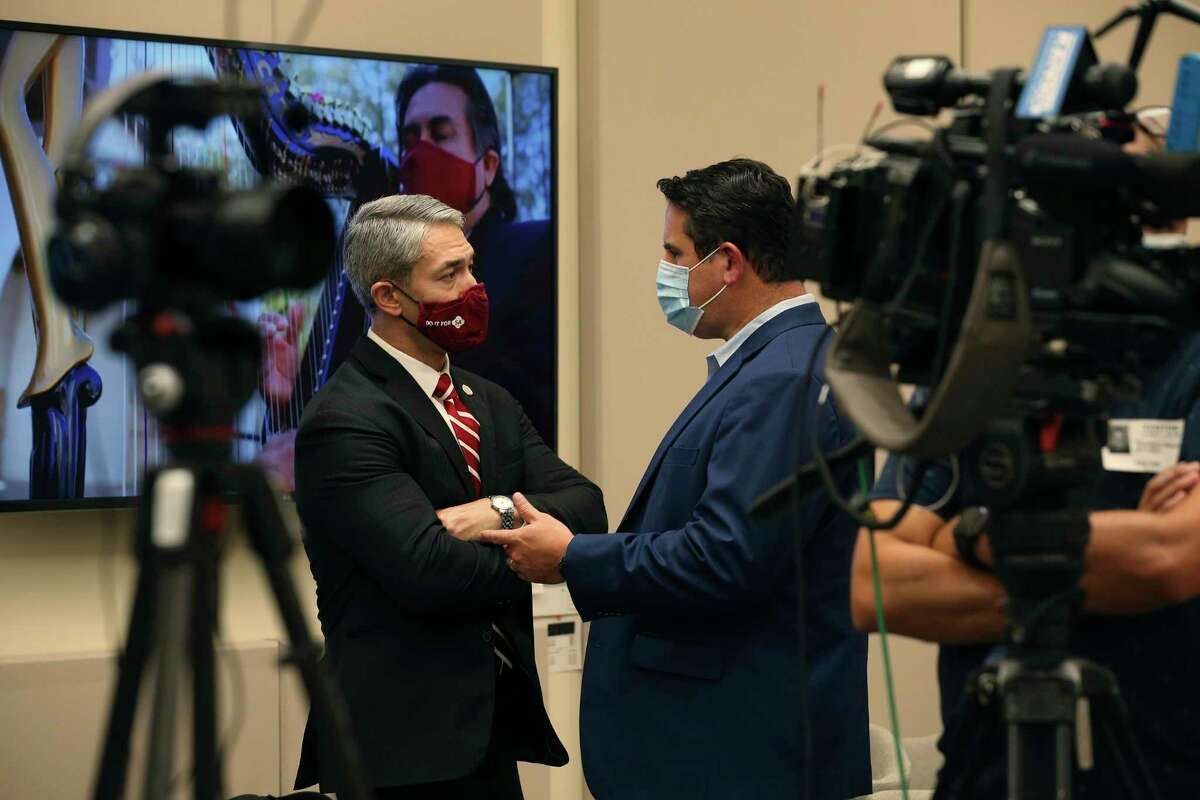 San Antonio Mayor Ron Nirenberg, left, talks with City Manager Erik Walsh before the start of a press conference at City Hall, Wednesday, July 28, 2021. Local officials urged the public to get the COVID-19 vaccine and everyone, vaccinated or not, wear face masks indoors.