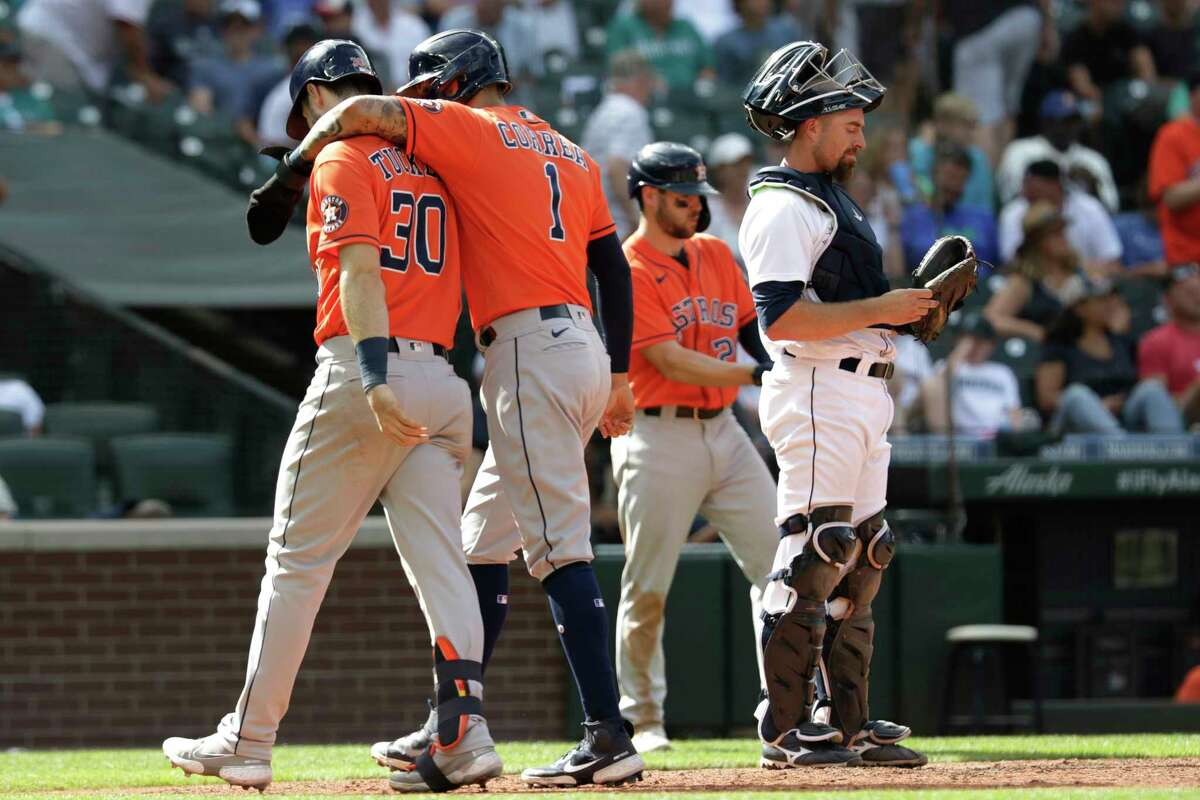 Houston Astros' Carlos Correa welcomes teammate Kyle Tucker as they cross home plate next to Seattle Mariners catcher Tom Murphy following Tucker's two-run home run during the eighth inning of a baseball game Wednesday, July 28, 2021, in Seattle. (AP Photo/Jason Redmond)