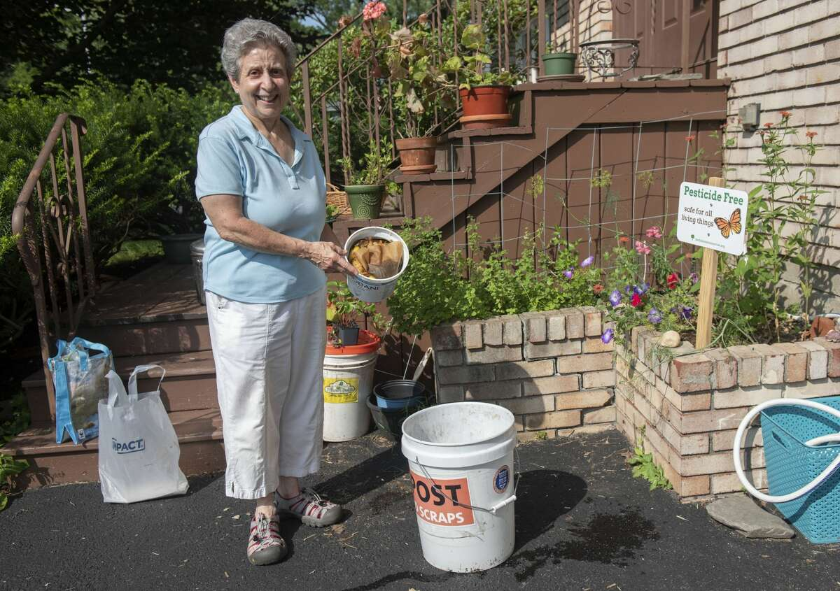 Audrey Seidman dumps her food scraps into a compost pail in her friend's driveway on Thursday, July 22, 2021 in Albany, N.Y. When the bucket gets full her friend Tina Lieberman brings it to the backyard and dumps it in the compost pile for her garden. This is one way anyone can honor the mystical year of release;