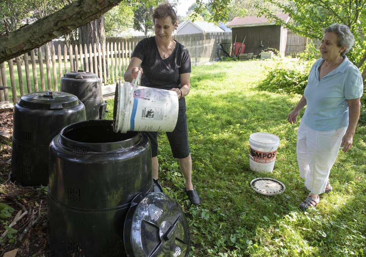 Audrey Seidman, right, watches her friend Tina Lieberman as she dumps food scraps into a compost pile in Lieberman's backyard on Thursday, July 22, 2021 in Albany, N.Y. Seidman brings Lieberman her food scraps. Leiberman uses the compost for her garden.