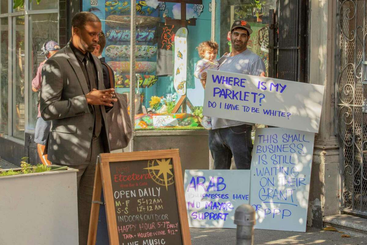 Eiad Eltawil (right) co-owner of Yasmin, a Mediterranean restaurant, holds a sign as Mayor London Breed signs legislation at a table inside Etcetera Wine Bar to make the city's parklets permanent.