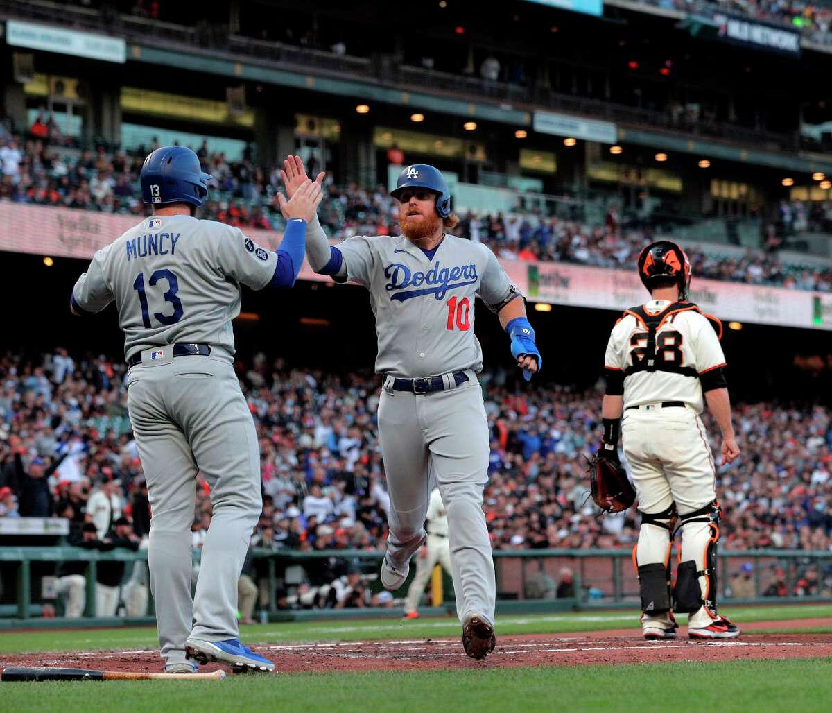 Max Muncy high fives Dodgers teammate Justin Turner after they scored on a Will Smith triple in the third inning.
