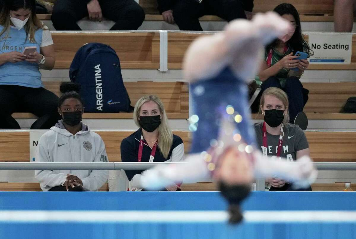 Simone Biles watches teammate Sunisa Lee performing on the uneven bars during the individual all-around final. Lee edged Brazil's Rebeca Andrade to win gold.