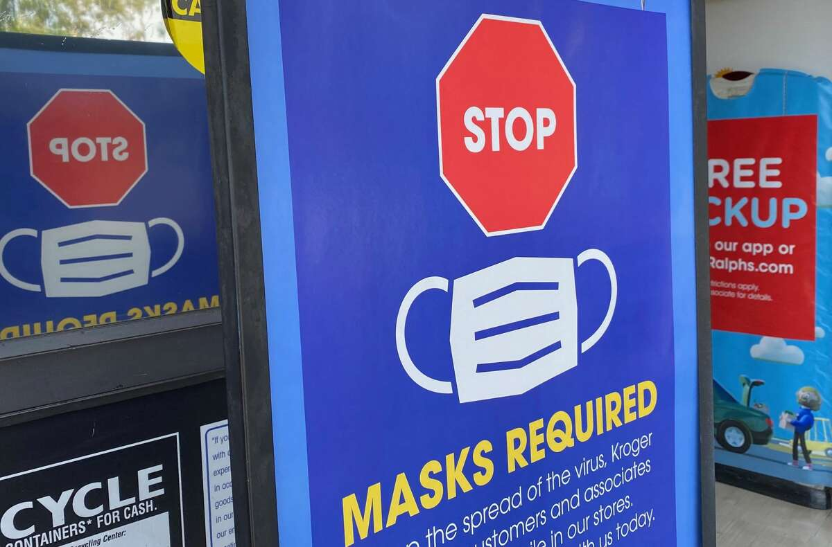 FILE -- A sign is posted at the entrance of a store telling people not to enter without a mask in Los Angeles on July 23, 2021. (Photo by CHRIS DELMAS/AFP via Getty Images)