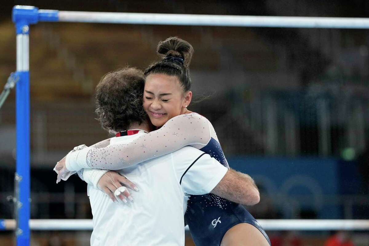 Sunisa Lee, of the United States, embraces her coach Jeff Graba after performing on the uneven bars during the artistic gymnastics women's all-around final at the 2020 Summer Olympics, Thursday, July 29, 2021, in Tokyo.