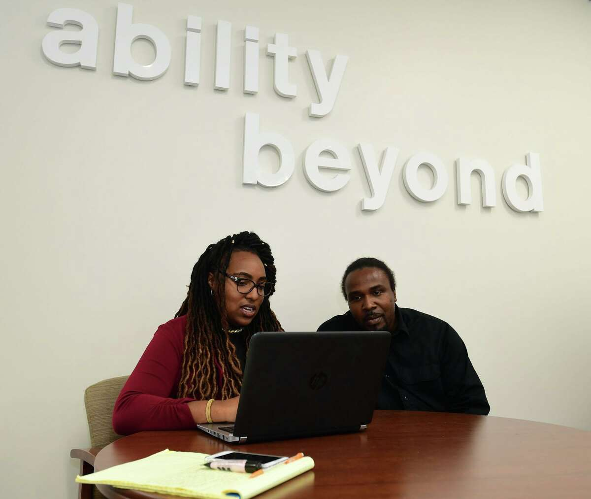 Employment Specialist Chenelle helps client Earl Melton at The Bethel-based disabilities services giant, Ability Beyond facility in Norwalk, Conn.