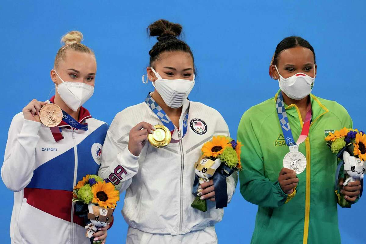 From right to left, silver medallist Brazil's Rebeca Andrade, Gold medallist Sunisa Lee of the Unites States, and bronze medallist Angelina Melnikova, of the Russian Olympic Committee, celebrate during the medal ceremony for the artistic gymnastics women's all-around at the 2020 Summer Olympics, Thursday, July 29, 2021, in Tokyo. (AP Photo/Natacha Pisarenko)