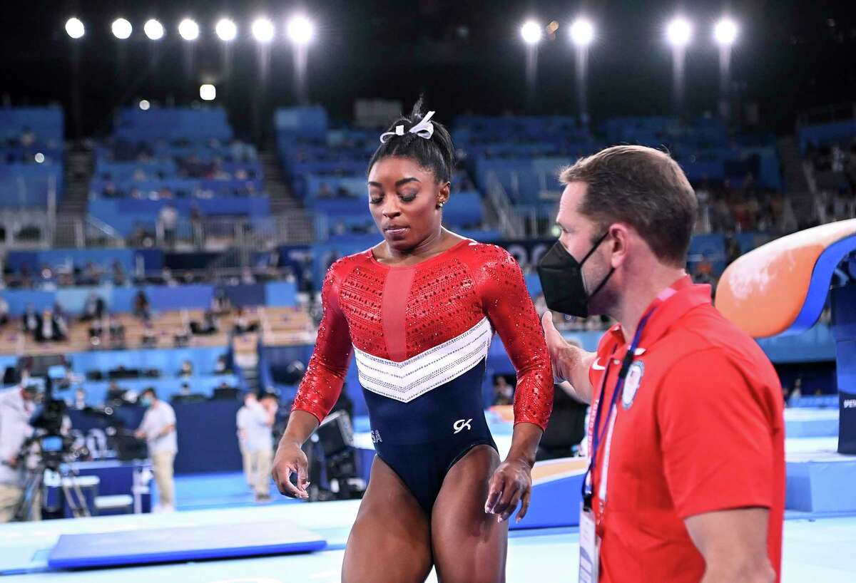 U.S. gymnast Simone Biles is consoled after competing on the vault and withdrawing from competition due to an injury in the women's team final at the 2020 Tokyo Olympics on Tuesday, July 27, 2021, in Tokyo, Japan. (Wally Skalij/Los Angeles Times/TNS)