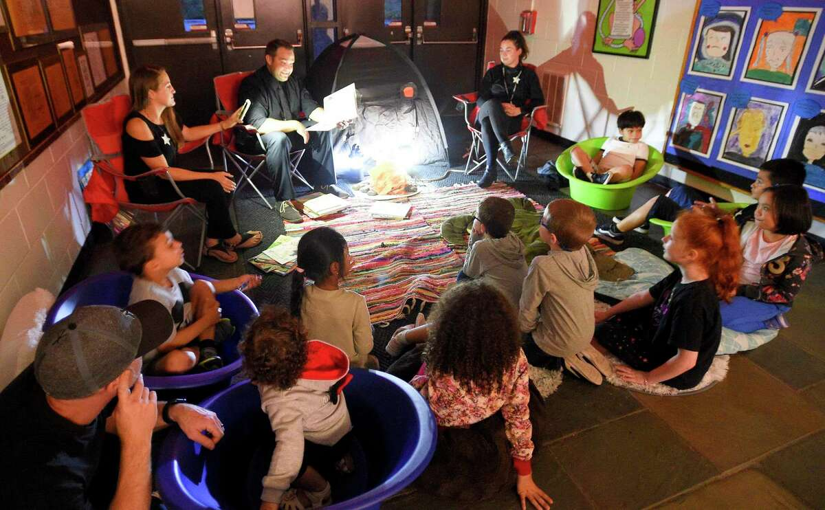 Randy Bilik, center, an SRBI instructor, reads to children and parents gathered around a pretend campfire at Stillmeadow Elementary School's annual Reading Under The Stars Family Literacy Night on Sept. 24, 2019. On Aug. 2, 2021, Bilik will take over as assistant principal at Newfield Elementary, where former assistant principal Sharon Longo was promoted to principal.