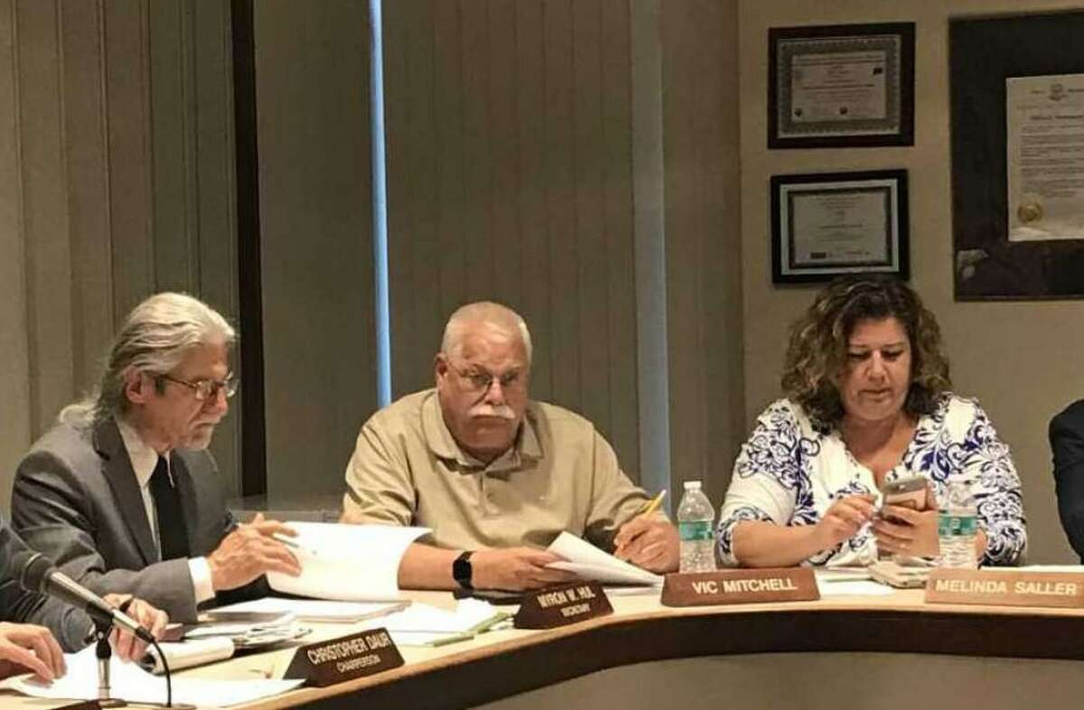 Board of Education member Melinda Saller, right, with then-colleagues Vic Mitchell, center, and Myron Hull, left, in 2019. Saller, who later became the board's secretary, announced she would run for town clerk in 2021.