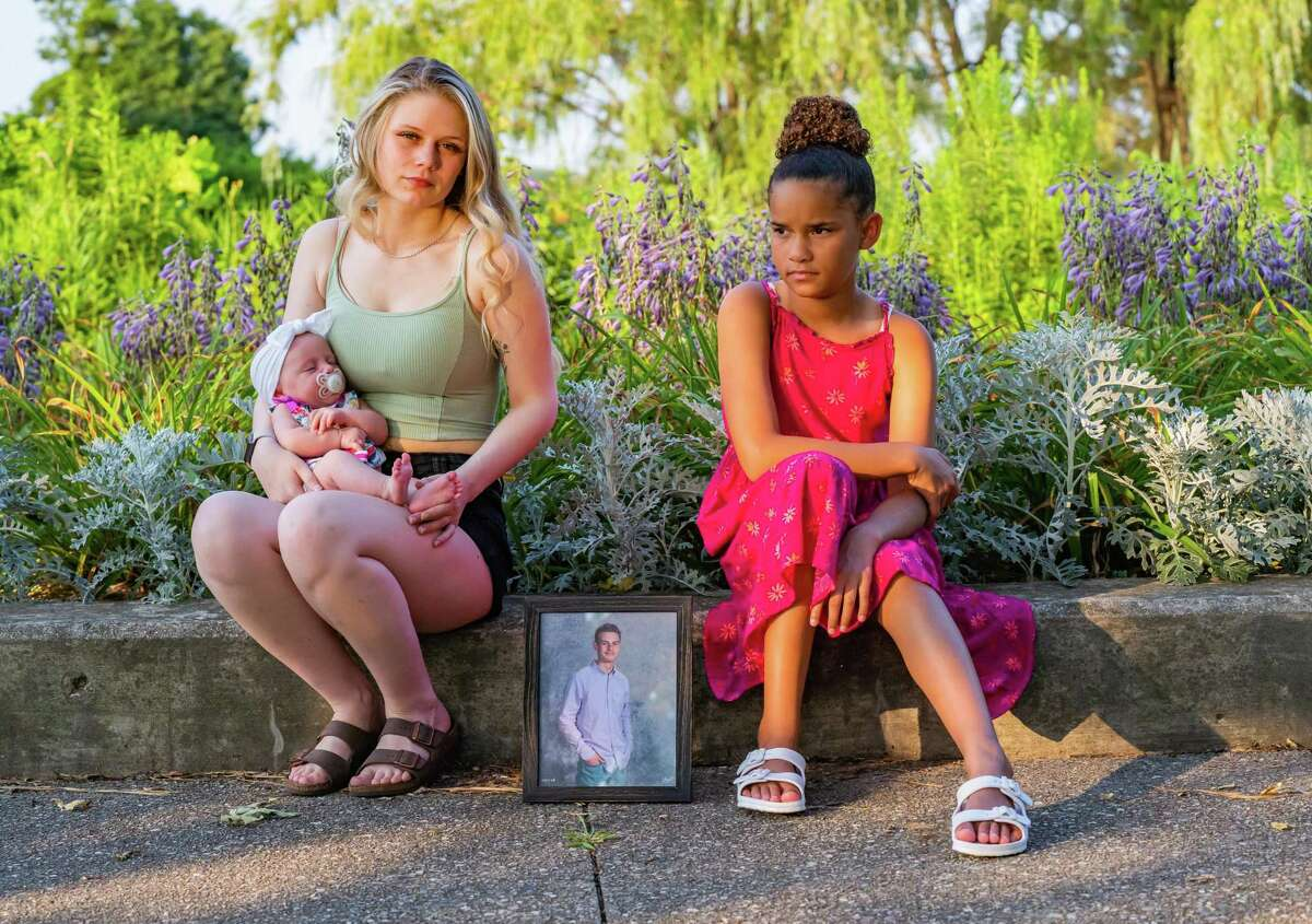 Abigail LeTourneau, left, holds her infant daughter Eliyanna as she sits for a portrait with her sister Adreanna Zavala at Elizabeth Park in Trenton, Michigan on July 27, 2021. Their brother Austin LeTourneau died from a fentanyl overdose in Houston last year. Elizabeth Park was one of his favorite places to visit.