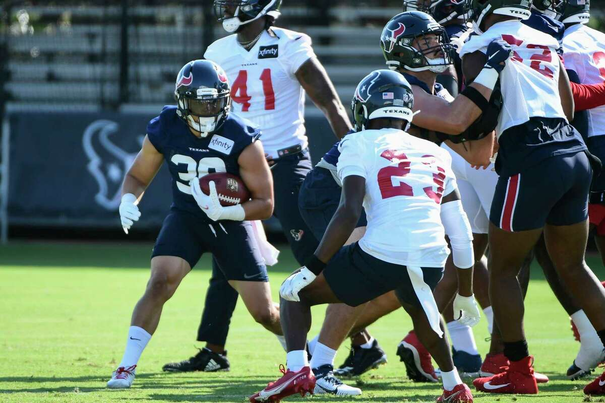Houston Texans running back Phillip Lindsay (30) runs the ball against defensive back Eric Murray (23) during NFL football practice Wednesday, July 28, 2021, in Houston. (AP Photo/Justin Rex)