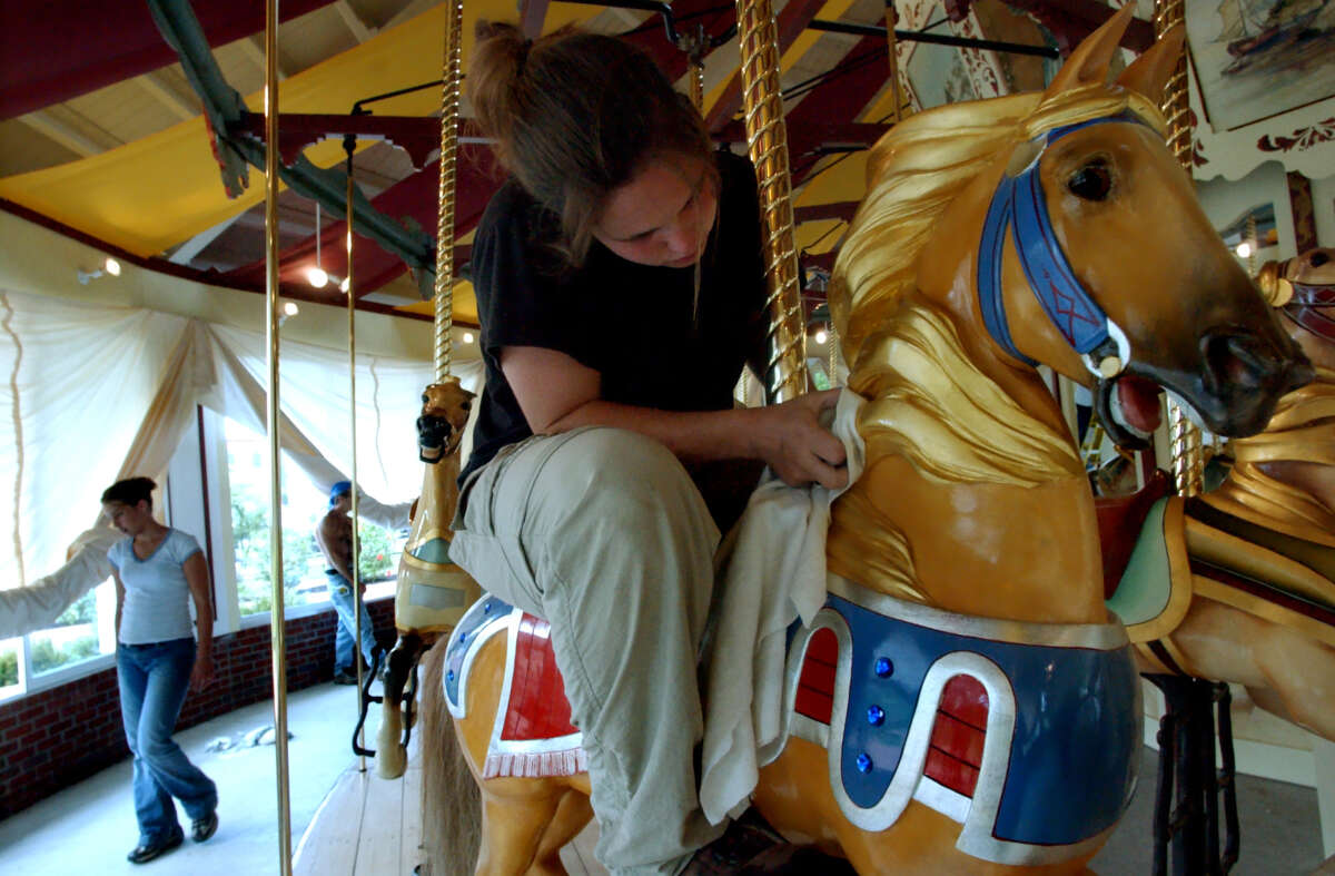 J'mae Shemroske, a public works employee, polishes a carousel horse before the grand opening Friday, June 28, 2002, at Congress Park in Saratoga Springs, N.Y. (Times Union staff photo by Cindy Schultz)