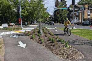 Biker rides along new protected bike lanes in Seattle's Green Lake neighborhood.