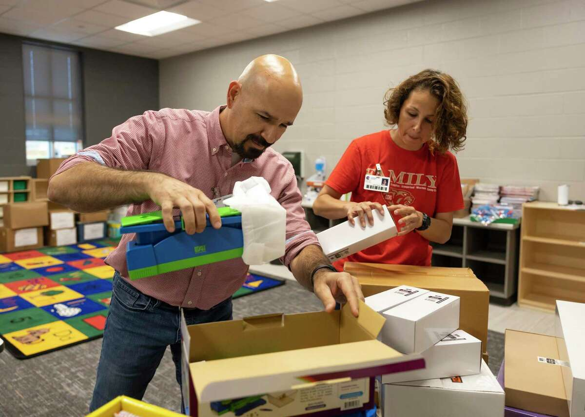 """Laura Garza, bilingual kindergarten teacher, right and principal Gilberto Lozano, open boxes in a classroom during a """"Pallet Party"""" in Hope Elementary, Thursday, July 22, 2021, in Conroe. Pallets of supplies were delivered to Hope Elementary to assist teachers and staff in preparation for the upcoming school year."""
