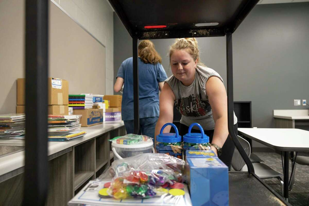 """Kaitlin Springer, kindergarten teacher. grabs boxes of supplies in a classroom during a """"Pallet Party"""" in Hope Elementary, Thursday, July 22, 2021, in Conroe. Pallets of supplies were delivered to Hope Elementary to assist teachers and staff in preparation for the upcoming school year."""
