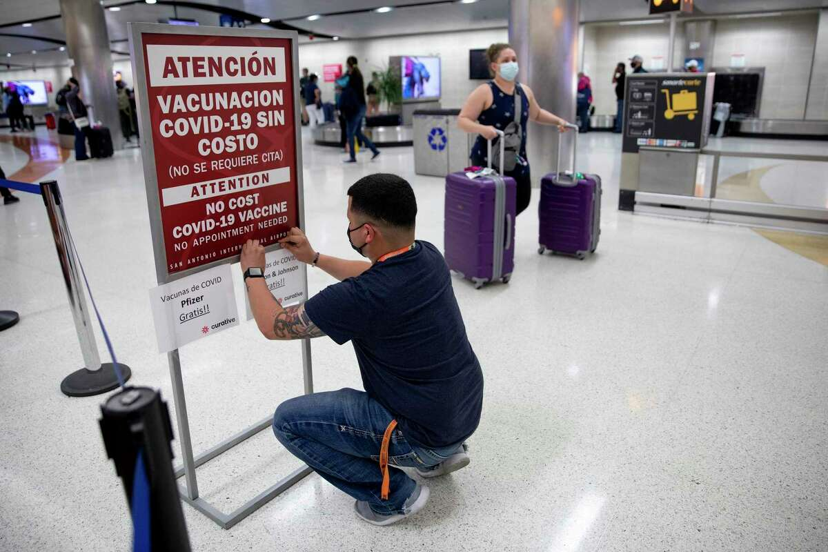 An employee of Curative tapes a list announcing which vaccines were available at a pop up COVID-19 vaccine clinic at the San Antonio International Airport.