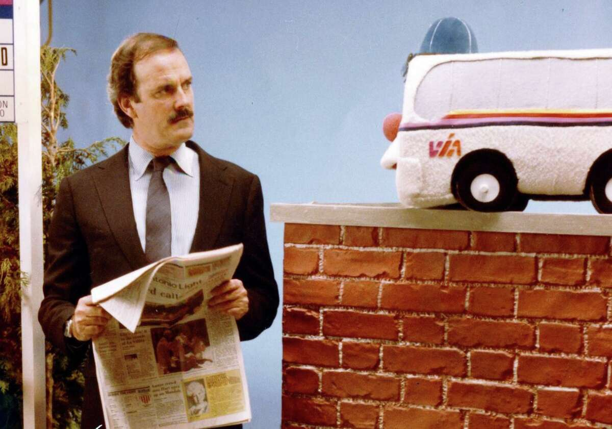 """John Cleese shares a scene with Buster the VIA Buppet in the 1980s. The """"Monty Python"""" star appeared in several VIA ads and insisted on helping craft the scripts."""