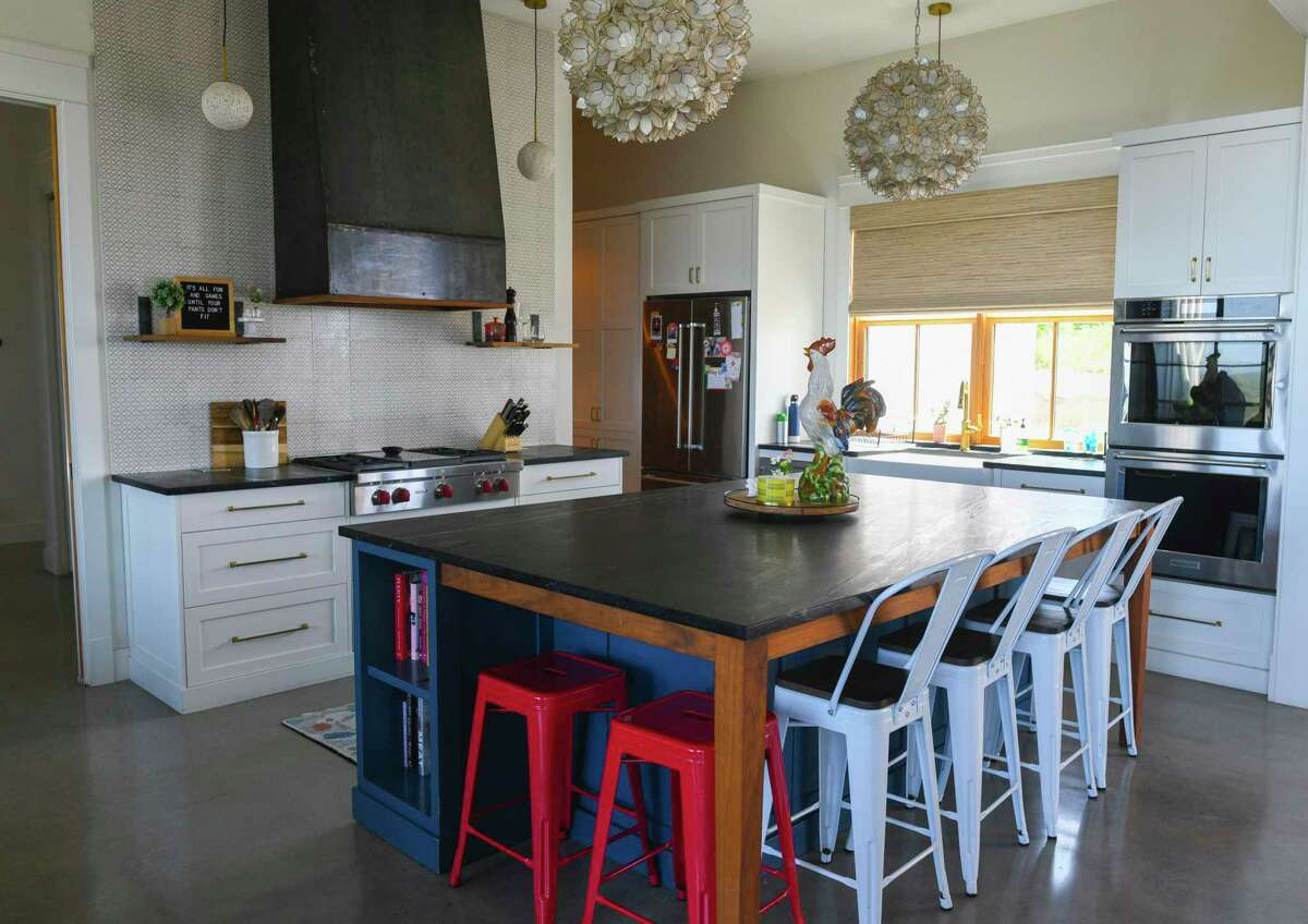 The kitchen island in the kitchen Carey and Regan Meador has a soapstone top and deep overhand so family and friends can sit around it like it's a table.