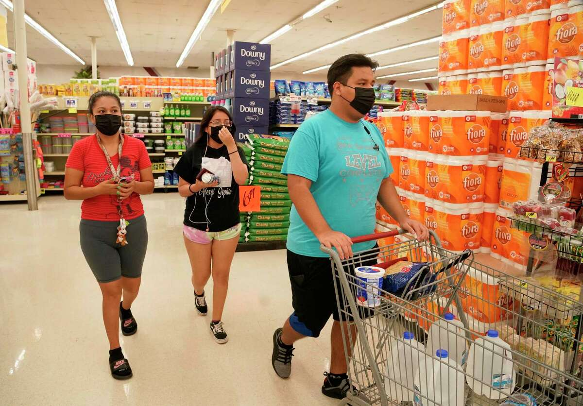 Josue Sanchez, 16, right, shops at Food Town, 5367 Antoine Dr., Tuesday, July 27, 2021 in Houston as the Houston Health Department holds a vaccination event in the store.
