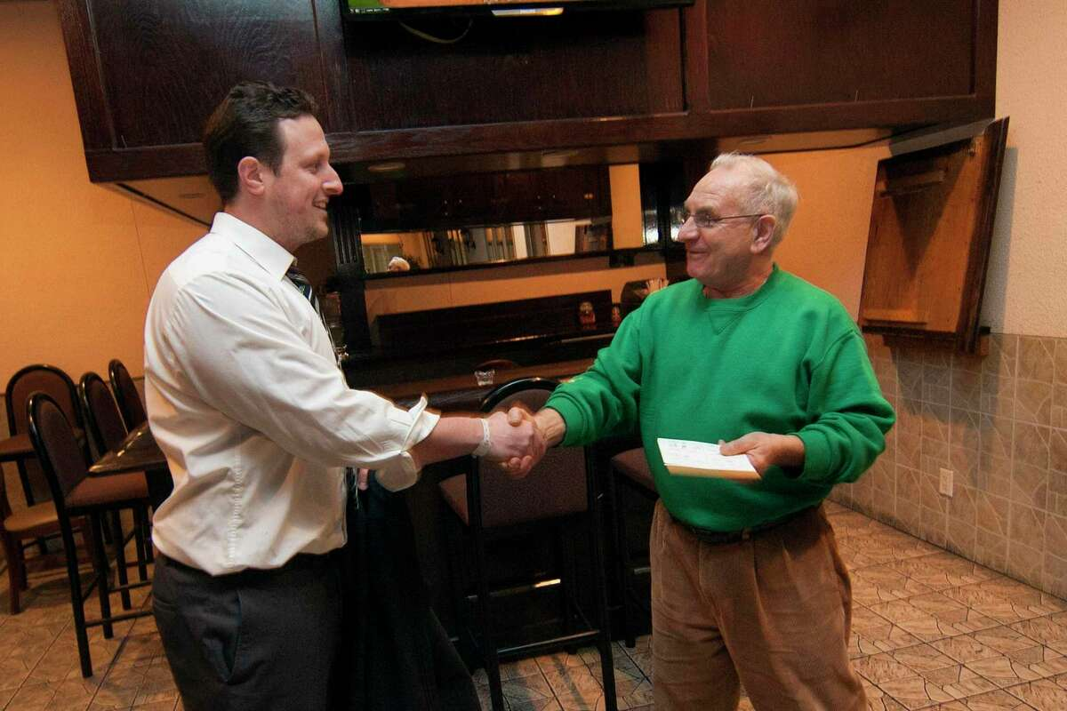 Candidate Michael DeFilippo, left, is congratulated by DTC Chair Mario Testa at Testo's Restaurant after the polls closed for the primary election for the 133rd District in Bridgeport, Conn., on Tuesday Apr. 10, 2018.