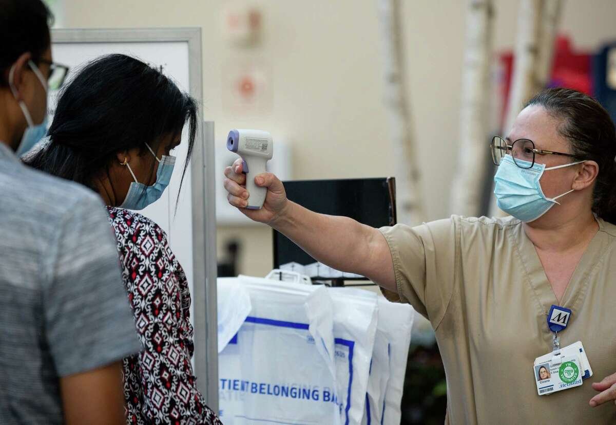 Health screener Eliziana Amud, right, checks the temperature of people entering the Houston Methodist West Hospital on Wednesday, July 28, 2021, in Katy.