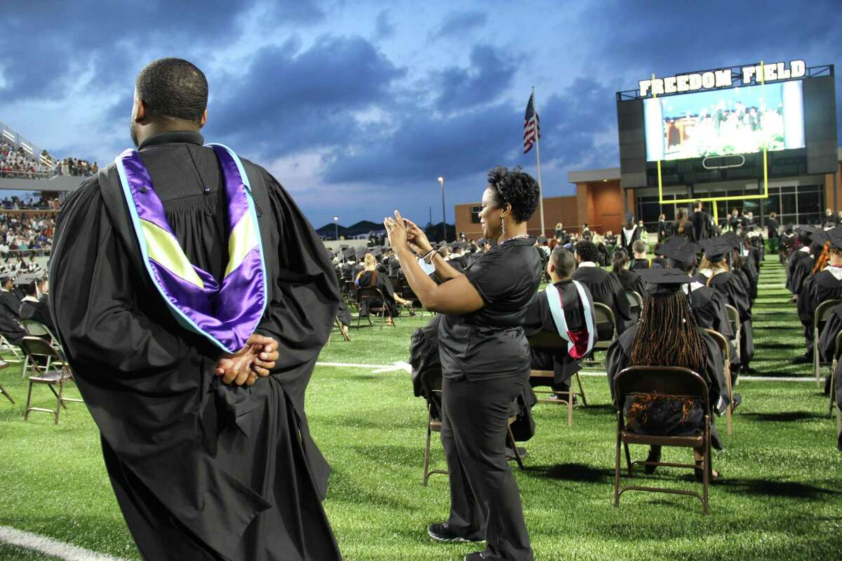 Shante Clark-Davis, campus communication liaison for Shadow Creek High School, takes photographs during graduation. The district recently named new communication liaisons for 33 campuses.