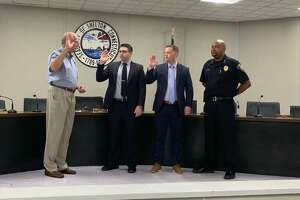 Mayor Mark Lauretti swears in new police officers Leonard Scinto and Colin Bitsco Tuesday, July 27, at City Hall as police Chief Shawn Sequeira looks on.
