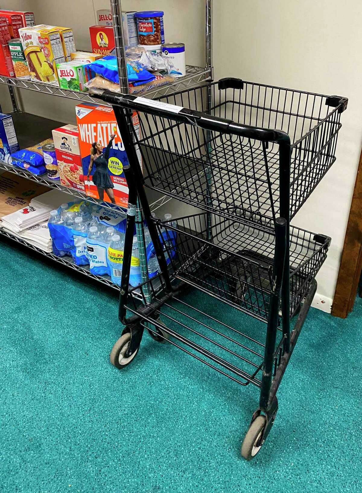 TheCaseville Community Food Pantry, located in the basement of Caseville United Methodist Church, features a shopping cart for those who need immediate help. The food pantry will continue to hold drive-thru food distributions after the pandemic is over, due to their efficiency and cost-effectiveness. (Mark Birdsall/Huron Daily Tribune)