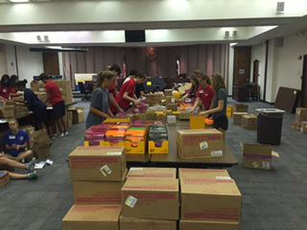 Spring Branch ISD student volunteers sort and package a room full of school supplies from a past year's Spring Branch Education Foundation's Project School Supplies