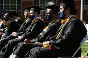 Graduates sit socially distant with masks on the quad for the Undergraduate and Graduate School of Business/School of Engineering Class of 2020 Commencement at Quinnipiac University in Hamden on May 15, 2021.
