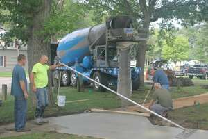 Workers from Washaw Construction spread and smooth concrete as it is poured by Team Elmer's Concrete for a new sidewalk at Rietz Park in Manistee. The sidewalk will make the restrooms more accessible for those with mobility issues.