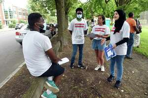 From left, Aaron Moody of New Haven listens to Public Health College Corps members Taylor Munroe Kripa Patel and Nour Al Zouabi at De Gale Field in New Haven on July 29, 2021, about passing along literature concerning COVID-19 vaccinations to friends and family.