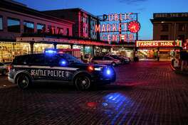 A police vehicle follows behind a group of demonstrators near Pike Place Market as they protest the death of Daunte Wright on April 12, 2021 in Seattle, Washington.