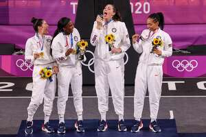 Tokyo, Japan, Wednesday July 28 2021 - USA 3x3 teammates laugh as Stefanie Dolson pretends to lick her Gold Medal in the Womens 3x3 Final at Aomi Urban Sports Park. Left to right are Kelsey Plum, Jaqueline Young, Doson and Allisha Gray. (Robert Gauthier/Los Angeles Times via Getty Images)