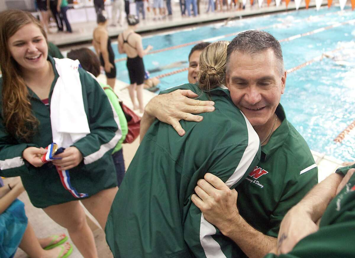 Woodlands head swimming and diving coach Kent Kirchner hugs diver Kendall McClenney after she placed third in the girls 1 meter diving while Woodlands state champion diver Kelly Markle looks on at the UIL State Swimming and Diving Championships in Austin on Saturday.