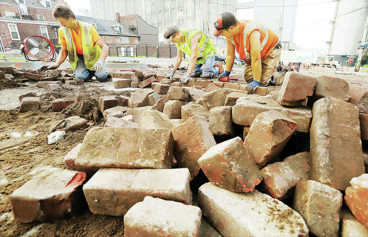 """Stutz Excavating, Inc., workers on Thursday were replacing the bricks - one at a time - on Williams Street in Alton. The street was repaired from damage caused in the Flood of 2019. Williams Street is on a list of """"protected"""" streets designated by the Alton City Council that requires bricks to be replaced after any repair."""