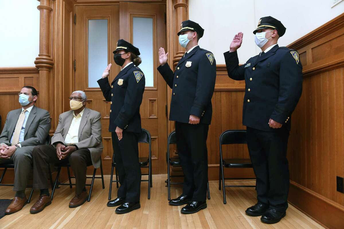 From left, New Haven police officers Rose Dell, John Healy and David Zannelli take the oath of office during a Captain Promotions ceremony at City Hall in New Haven on July 29, 2021.