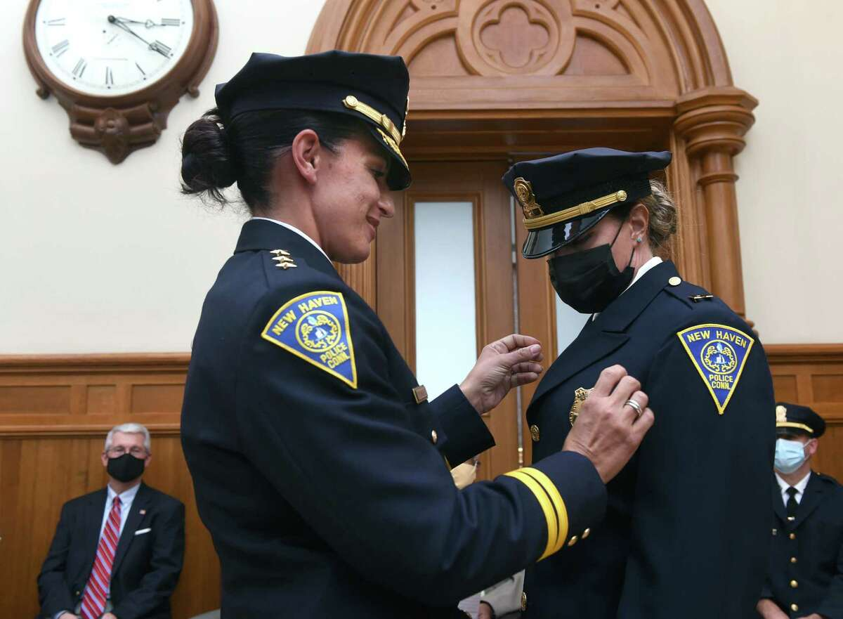 Interim New Haven Police Chief Renee Dominguez, left, pins a captain badge on Rose Dell during a ceremony at City Hall in New Haven on July 29, 2021.