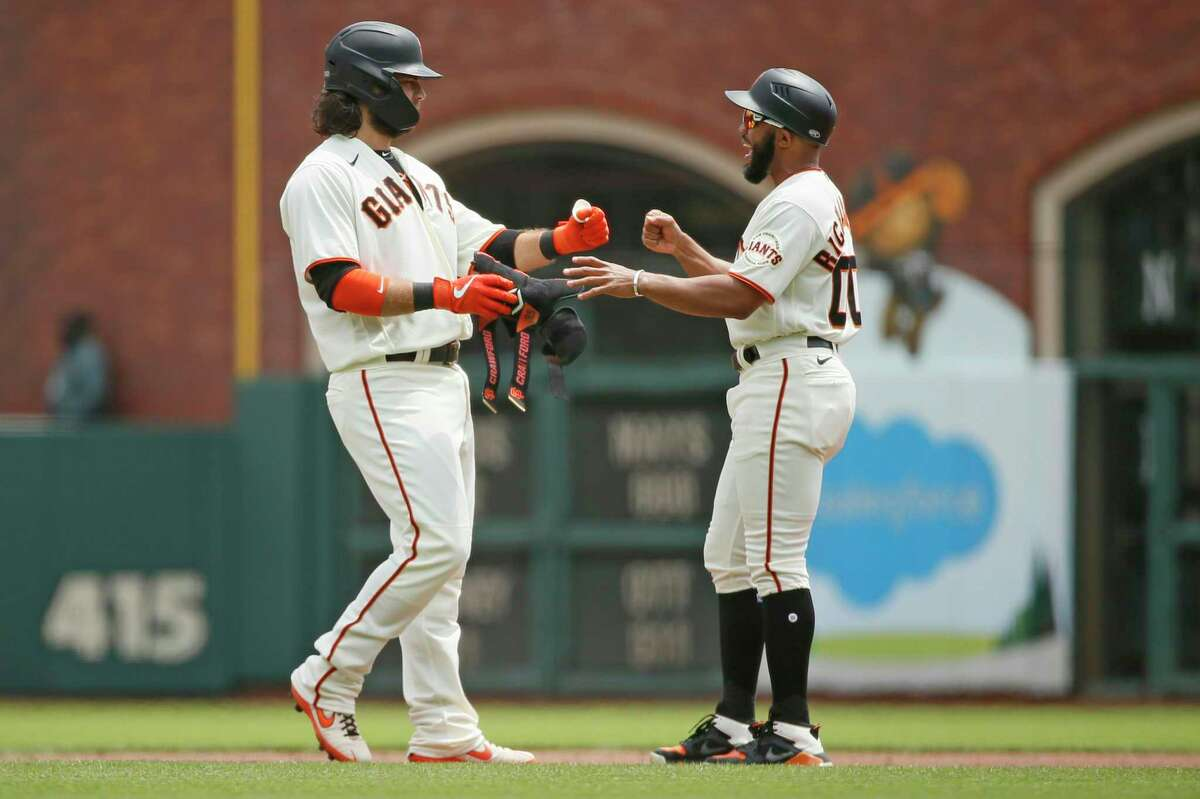 From left: San Francisco Giants Brandon Crawford (35) fist bumps first base coach Antoan Richardson (00) in the first inning during an MLB game at Oracle Park, Thursday, July 29, 2021, in San Francisco, Calif. Crawford hit a two-RBI double.