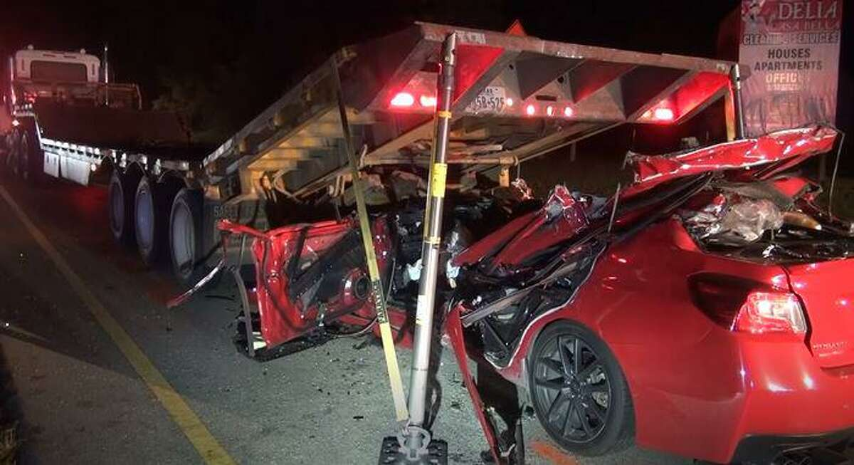 A vehicle described as a Subaru can be seen under a tractor trailer after its driver reportedly crashed into it Wednesday night near Lake Conroe and died on the scene.