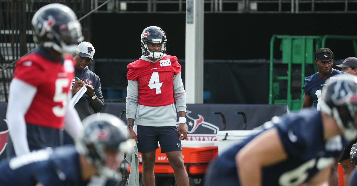 Houston Texans quarterback Deshaun Watson (4) stands on the sidelines as quarterback Tyrod Taylor (5) runs the offense during an NFL training camp football practice Thursday, July 29, 2021, in Houston.