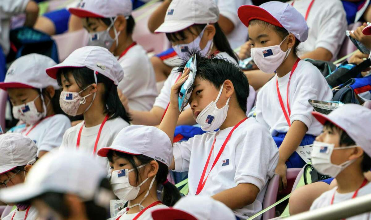 A boy holds an ice pack to his head to cool off while watching an Olympics soccer game at the Kashima Stadium in Ibaraki Prefecture, Japan, on Thursday, July 22, 2021. While fans have been barred from the majority of venues to contain coronavirus infections, three host prefectures are still allowing a limited number of spectators, mostly schoolchildren, at Olympic venues. (Doug Mills/The New York Times)