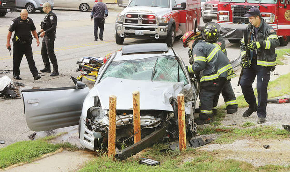 Alton firefighters use a hydraulic rescue tool Thursday afternoon to free the driver of a Mitsubishi Eclipse who collided with a Chevrolet Traverse in the 1100 block of Milton Road.
