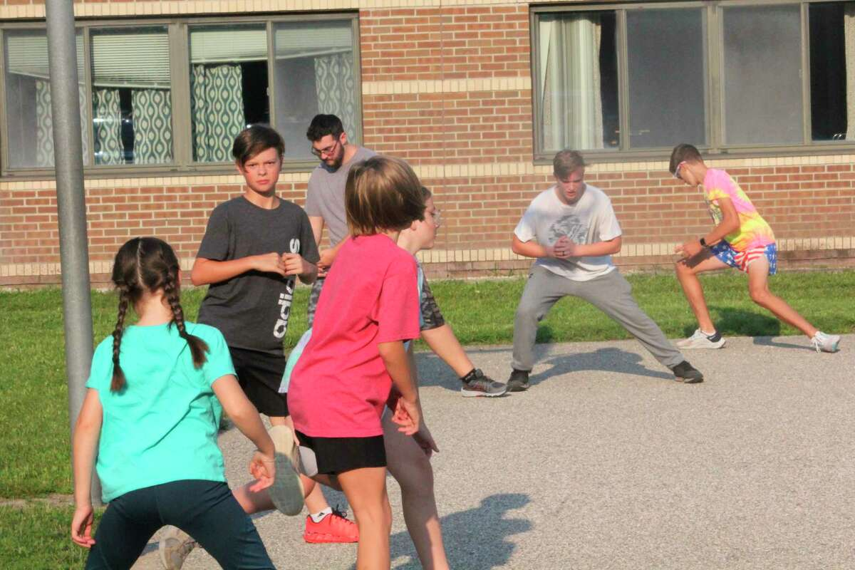 Reed City runners work out behind the middle school to get ready for a Tuesday night run. (Pioneer photo/John Raffel)