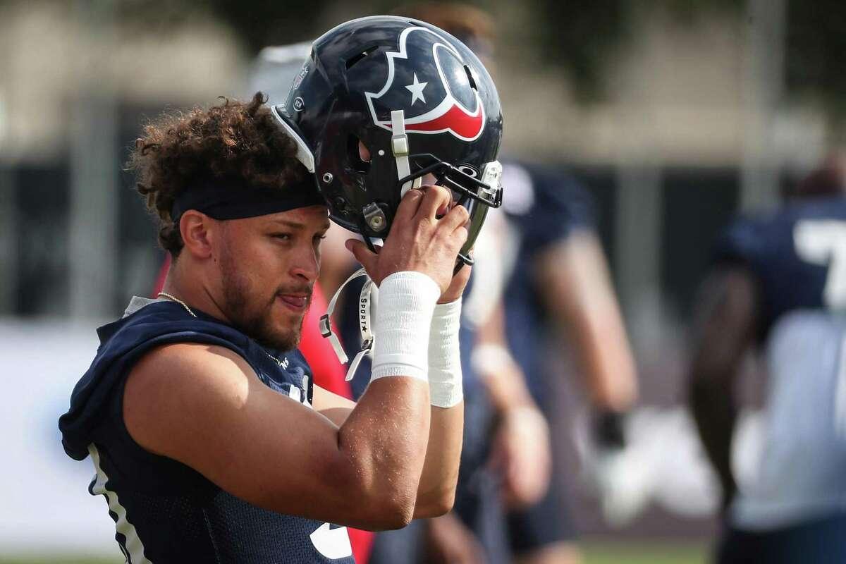Houston Texans running back Phillip Lindsay dons his helmet during an NFL training camp football practice Thursday, July 29, 2021, in Houston.