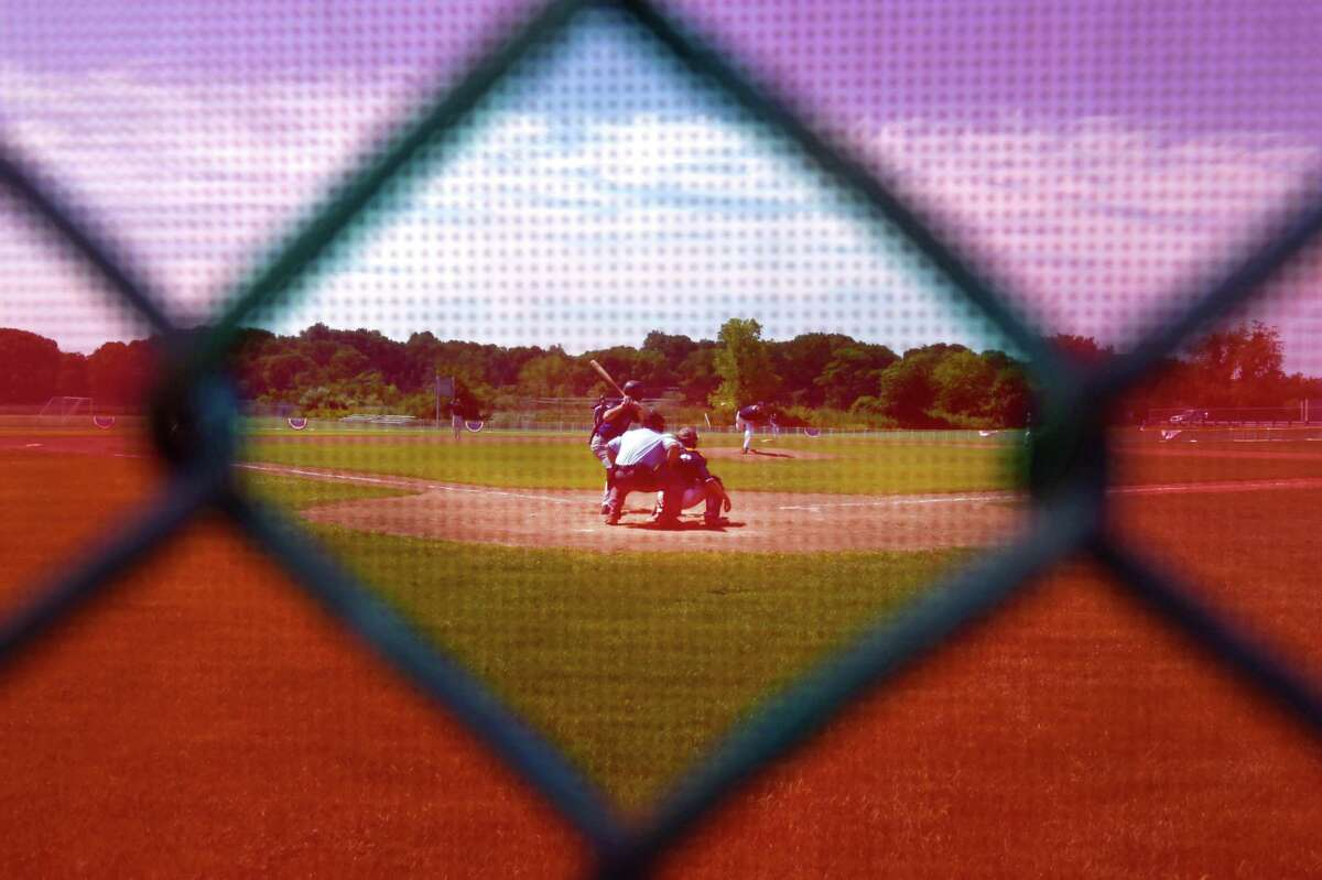 (Photo Illustration by Peter Hvizdak - New Haven Register) Looking through the a red mesh and wire fence backstop behind home plate, the Branford American Legion Post 83 and the East Haven American Legion Post 89 play a baseball game Saturday, July 11, 2015 at Branford High School's George T. Dummar Baseball Field.