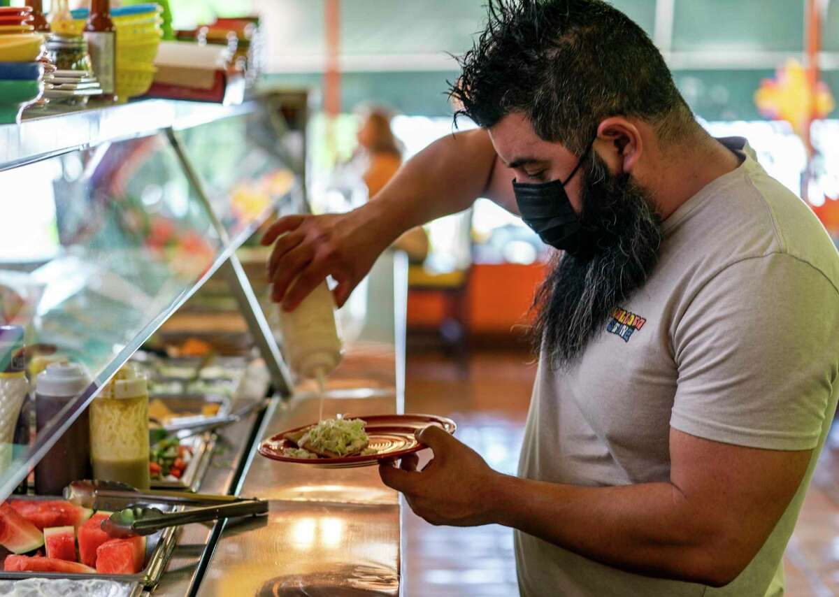Gustavo Arellano, 36, who is vaccinated, wears a face mask as he fixes himself a plate at Taqueria El Sol buffet in Los Angeles. Masks are required for everyone indoors in Los Angeles County, and parts of the Bay Area are considering whether to follow suit.