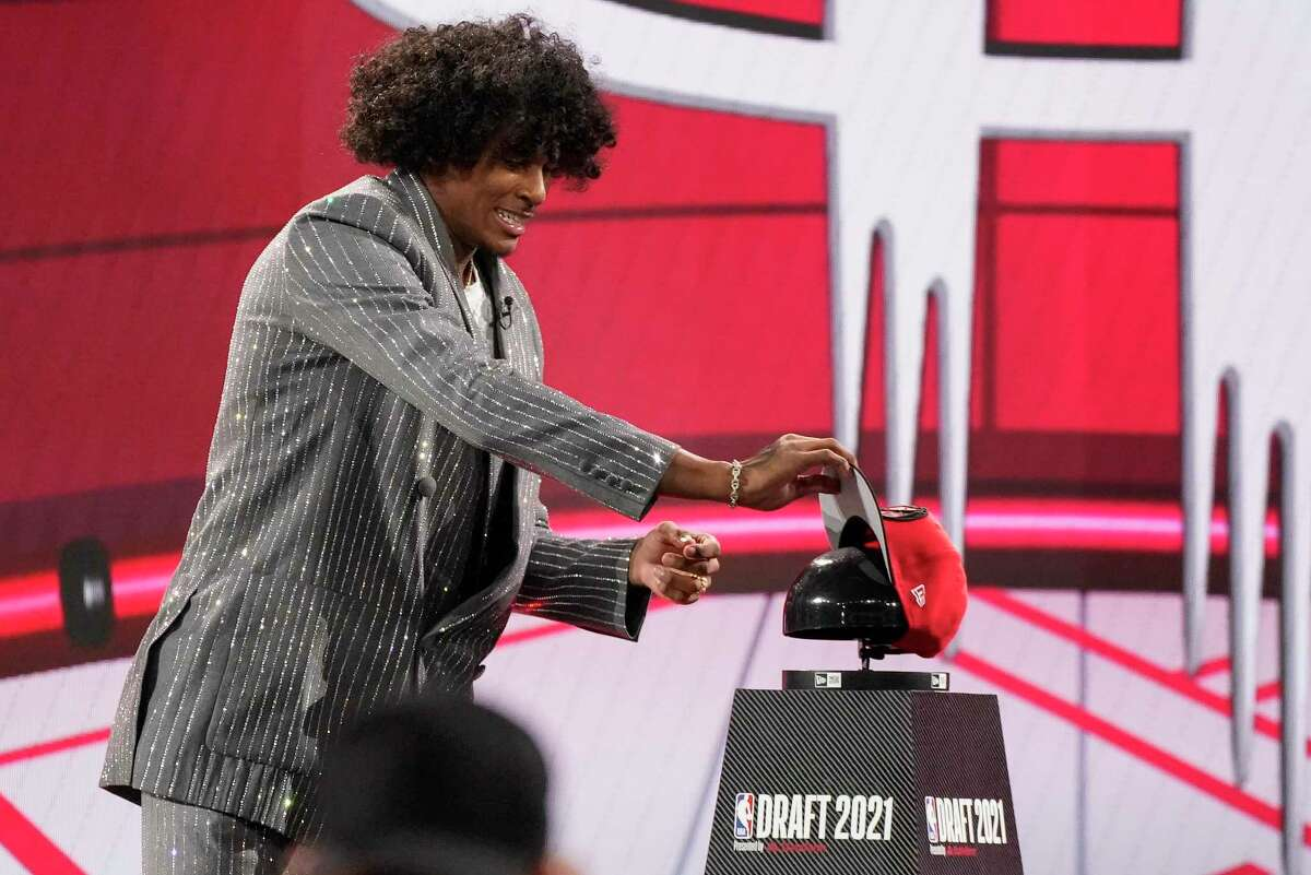 Jalen Green picks up a Houston Rockets cap after he was selected by the Houston Rockets as the second overall pick during the first round of the NBA basketball draft, Thursday, July 29, 2021, in New York.