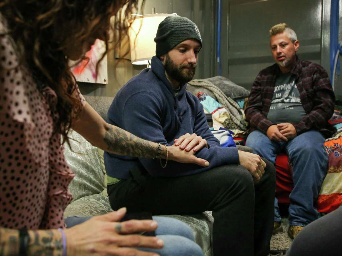 Casey Malish, center, holds Judy Germain's hand during a visit in Houston. Malich organizes and delivers harm reduction supplies for people who use opioids in the city.